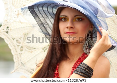 Portrait of an young lady in blue hat with an umbrella - stock photo