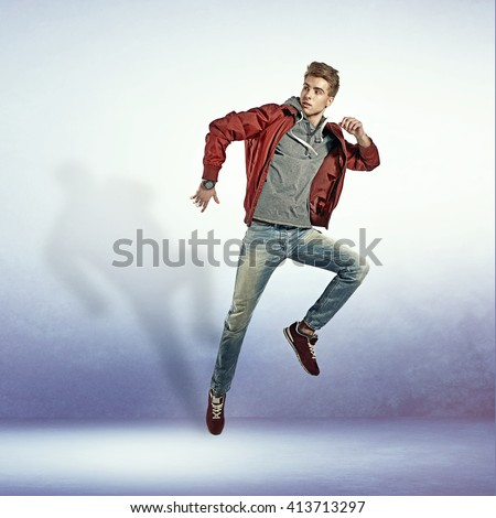 Portrait of an young man jumping in air - stock photo