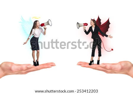 Portrait of angel and devil girls with megaphone standing on palms and copyspace between them on white background - stock photo
