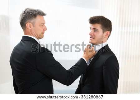 Portrait Of Angry Businessman Holding Young Businessman's Tie In Office - stock photo