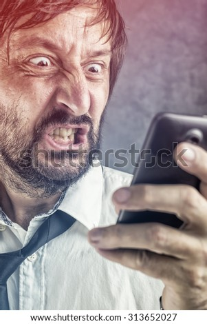 Portrait of angry businessman received frustrating SMS message or e-mail on mobile smart phone, selective focus on face - stock photo