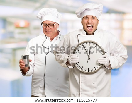 Portrait Of Angry Chef Holding Clock, Indoor - stock photo