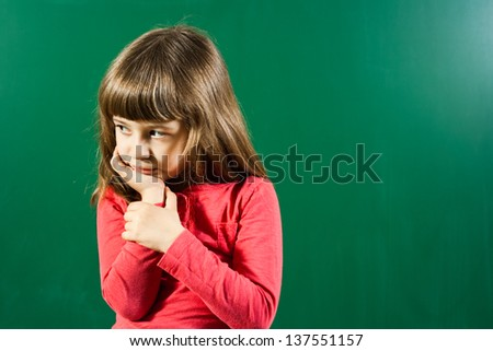 Portrait of angry little girl in front of blackboard,Angry little girl - stock photo