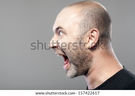 portrait of angry man screaming isolated on gray background with copyspace - stock photo