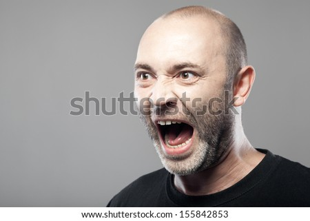 portrait of angry man sreaming isolated on gray background with copyspace - stock photo