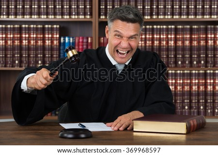 Portrait of angry mature judge striking his gavel at table in courtroom - stock photo