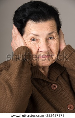 portrait of angry old woman grandmother covering her ears - stock photo