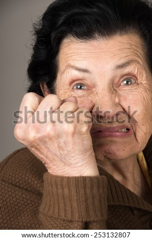 portrait of angry old woman grandmother holding her fist up - stock photo