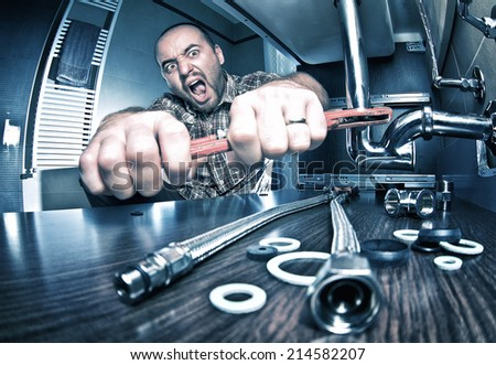 portrait of angry plumber at work - stock photo