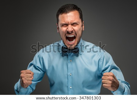 Portrait of angry upset young man in blue shirt and butterfly tie with fists up yelling isolated on gray studio background. Negative human emotion, facial expression. Closeup - stock photo