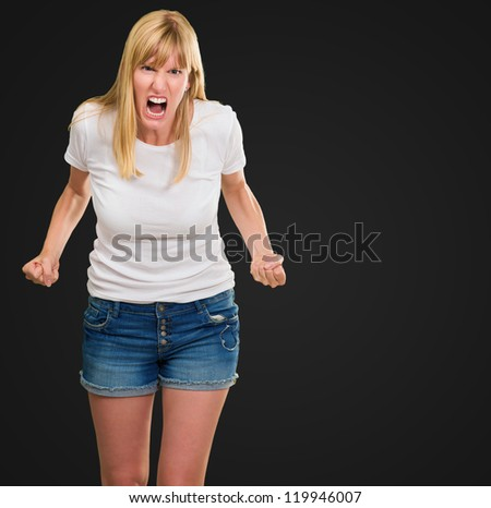 Portrait Of Angry Woman against a black background - stock photo