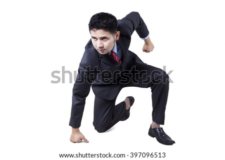 Portrait of angry young businessman punching the floor, isolated on white background - stock photo