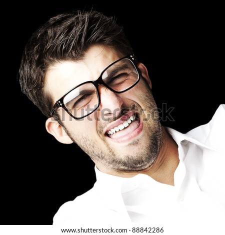 portrait of angry young man using tv control over black background - stock photo