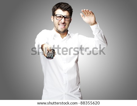 portrait of angry young man using tv control over grey background - stock photo