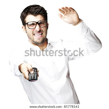 portrait of angry young man using tv control over white background - stock photo