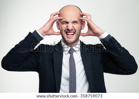 Portrait of annoyed depressed mad young business man in black suit isolated over white background - stock photo