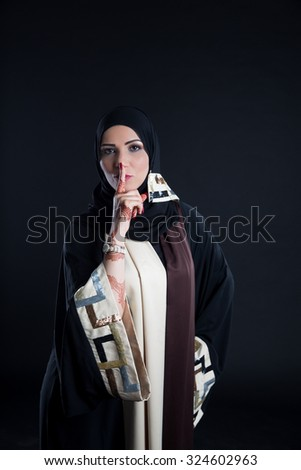 Portrait of Arab woman with finger on lips - stock photo