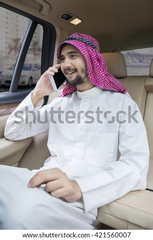 Portrait of Arabic businessman sitting on the seat back of the car while talking on the cellphone - stock photo