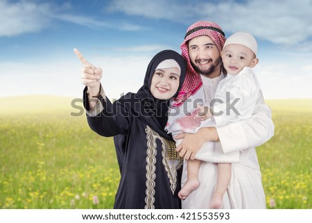 Portrait of Arabic woman with her husband and son, pointing at something at field - stock photo