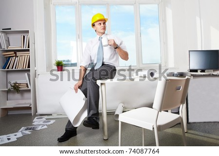 Portrait of architect in helmet drinking tea in office - stock photo