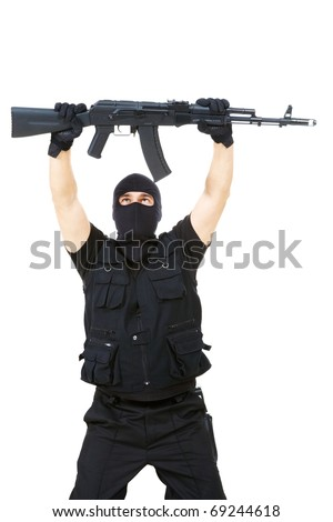 Portrait of armed assassin raising rifle in his hands over white background - stock photo