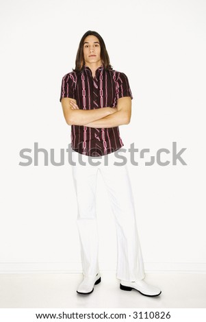 Portrait of Asian-American teen boy standing with arms crossed in front of white background. - stock photo