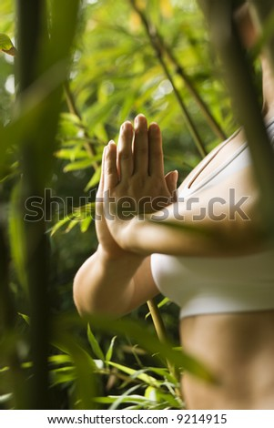 Portrait of Asian American woman in fitness attire standing in yoga position in bamboo forest in Maui, Hawaii. - stock photo