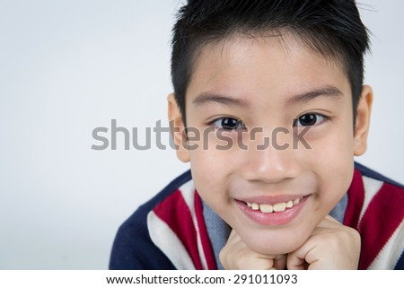 Portrait of asian boy with smile face wearing winter clothes on gray background - stock photo