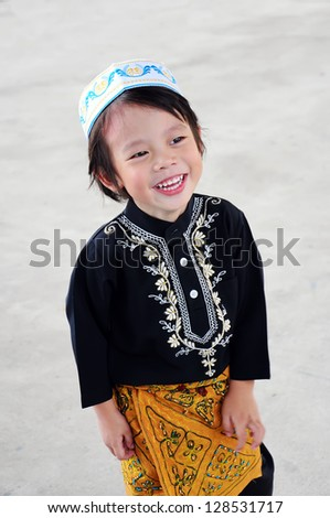 Portrait of asian boy with smile in malaysia dress - stock photo