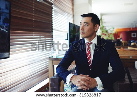 Portrait of asian businessman watching television while sitting in modern private room of the office, confident young professional dressed in elegant clothes relaxing in the armchair in interior - stock photo