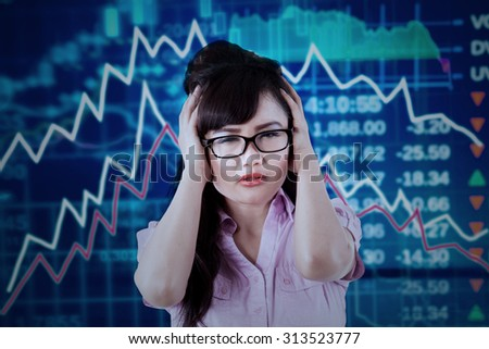 Portrait of asian businesswoman looks stressful with declining stock market - stock photo