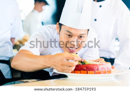 Portrait of Asian chef decorating cake - stock photo