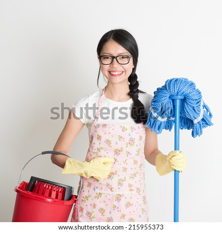 Portrait of Asian Chinese woman housekeeping, holding bucket and mop on plain background. - stock photo