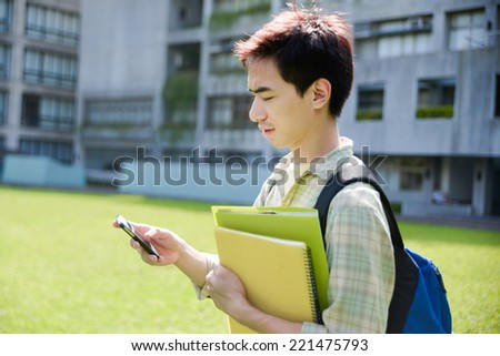 Portrait of Asian college student with a mobile phone in her hand at campus - stock photo