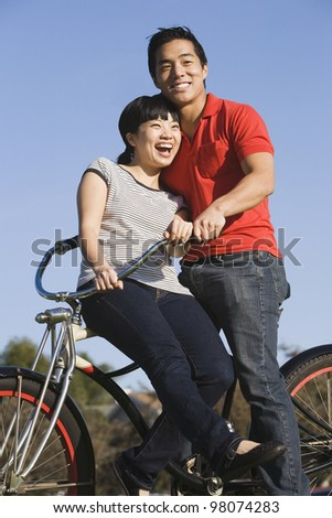 Portrait of Asian couple on bicycle - stock photo