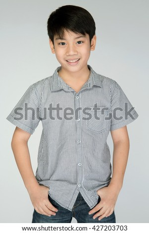Portrait of asian cute boy with smile face, on gray background - stock photo