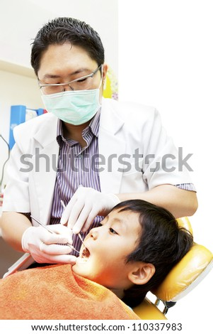 Portrait of asian dentist examining oral cavity of his patient at dental clinic - stock photo