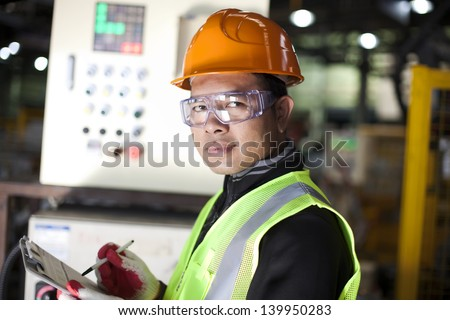 Portrait of asian engineer taking notes in the factory - stock photo