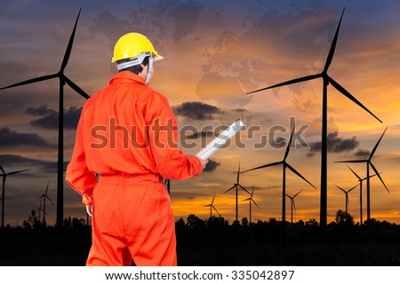 Portrait of Asian engineers holding at the blueprint on Wind turbine power generator with world map at twilight time, industrial concept, Elements of this image furnished by NASA - stock photo