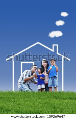 Portrait of asian family with dream house playing bubble outdoor - stock photo