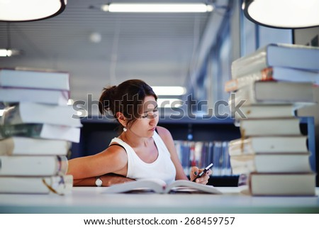 Portrait of asian female student sitting at the desk behind stack of books looking exhausted and tired to study, teenager sitting at the table with a huge pile of study books in university library - stock photo