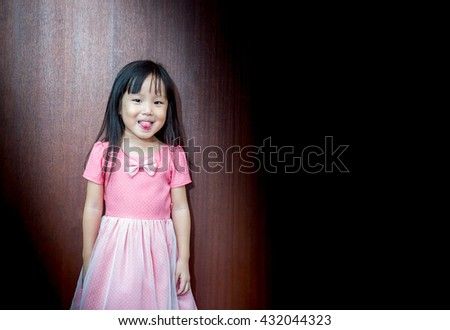 Portrait of Asian happy little girl, stick out her tongue - stock photo