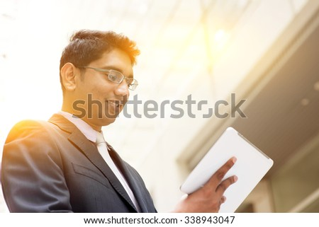 Portrait of Asian Indian business man using touch screen tablet computer, outside modern office building block, beautiful golden sunlight at background. - stock photo