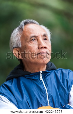 Portrait of Asian male senior looking away from camera. - stock photo