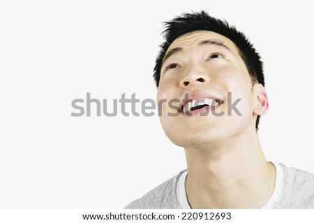 Portrait of Asian man looking up - stock photo