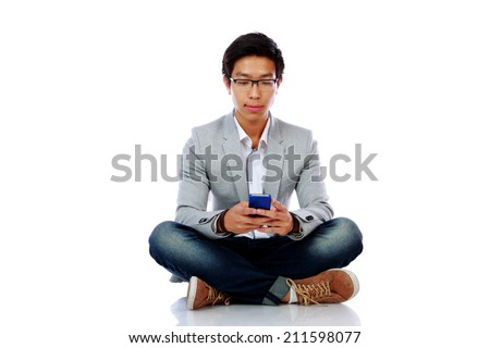 Portrait of asian man sitting on the floor and using smarpthone - stock photo
