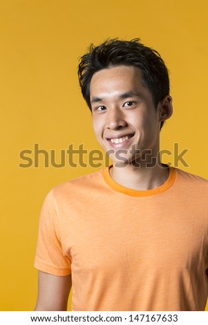 Portrait of Asian man standing against yellow background. - stock photo
