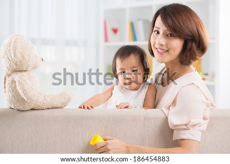 Portrait of Asian mother and daughter sitting on the sofa looking at the camera - stock photo