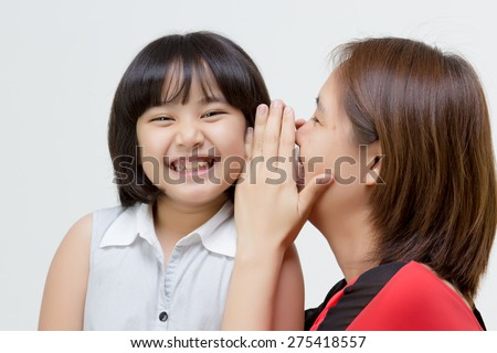 Portrait of Asian mother whispering to her daughter on isolated - stock photo
