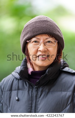 Portrait of Asian smiling female senior in winter clothing. - stock photo